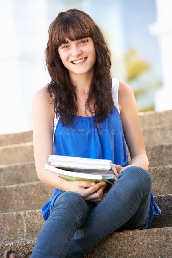 Estudiante adolescente que se sienta afuera en pasos de progresión de la universidad imagen de archivo