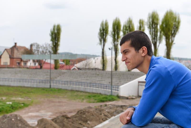 Estudiante adolescente que se sienta afuera en pasos del estadio imagen de archivo
