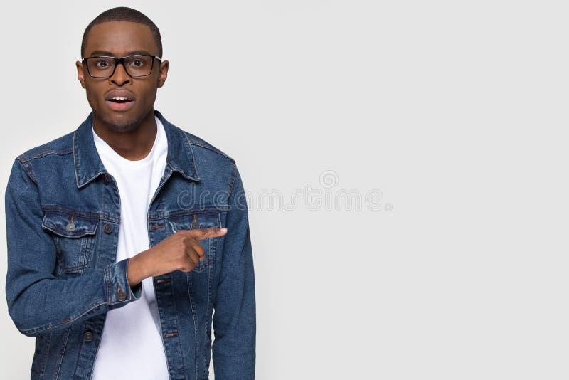 Estudiante africano chocado del hombre que señala el finger a un lado en el espacio de la copia imágenes de archivo libres de regalías