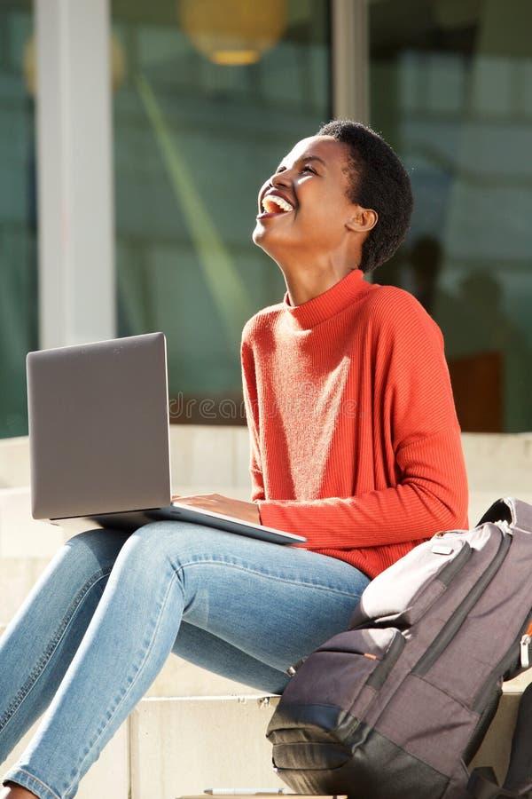 Estudiante africano feliz que trabaja con el ordenador portátil en campus de la universidad fotos de archivo libres de regalías