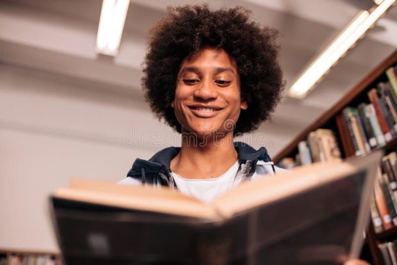 Estudiante africano joven que estudia en biblioteca imagenes de archivo