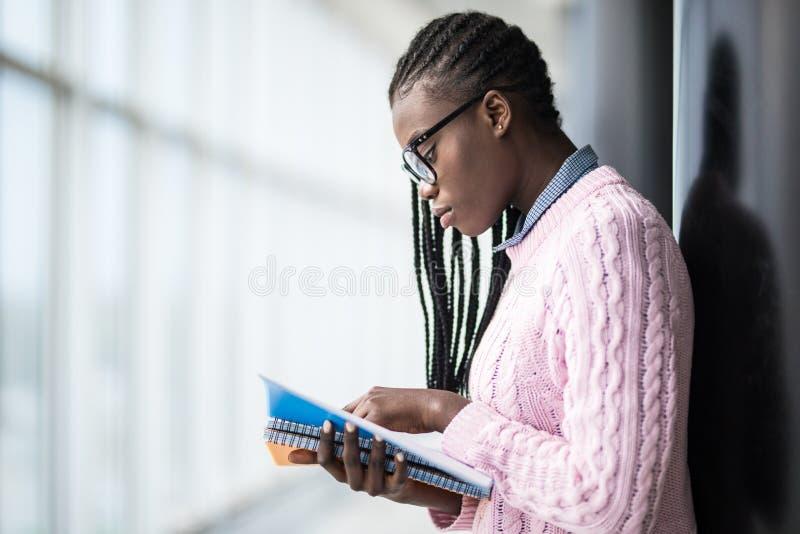 Estudiante afroamericana de la belleza joven en vidrios que lee los cuadernos y que estudia el nuevo objeto antes de conferencia  imagen de archivo libre de regalías
