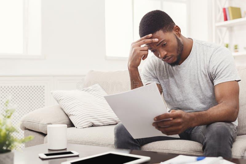 Estudiante afroamericano cansado joven que lee en casa foto de archivo