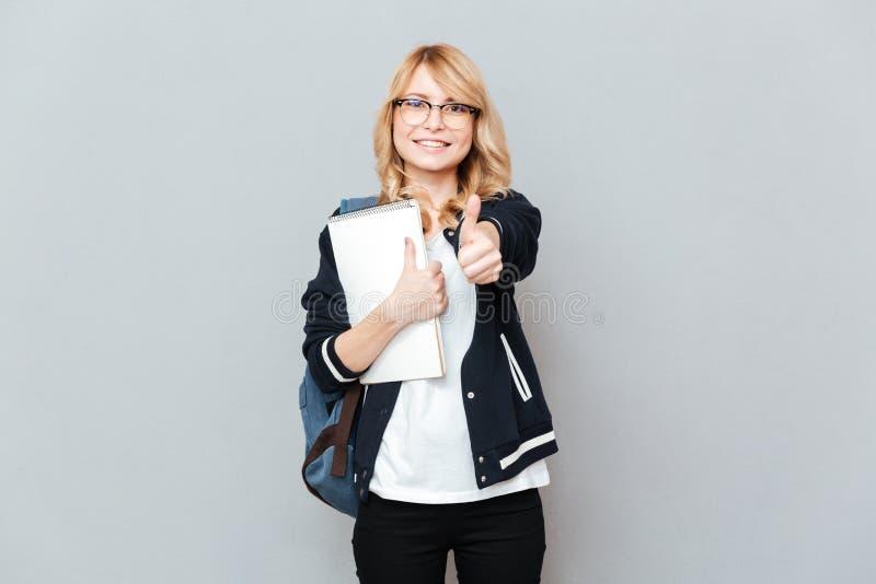 Estudiante alegre de la señora joven que sostiene el cuaderno que muestra los pulgares para arriba fotografía de archivo