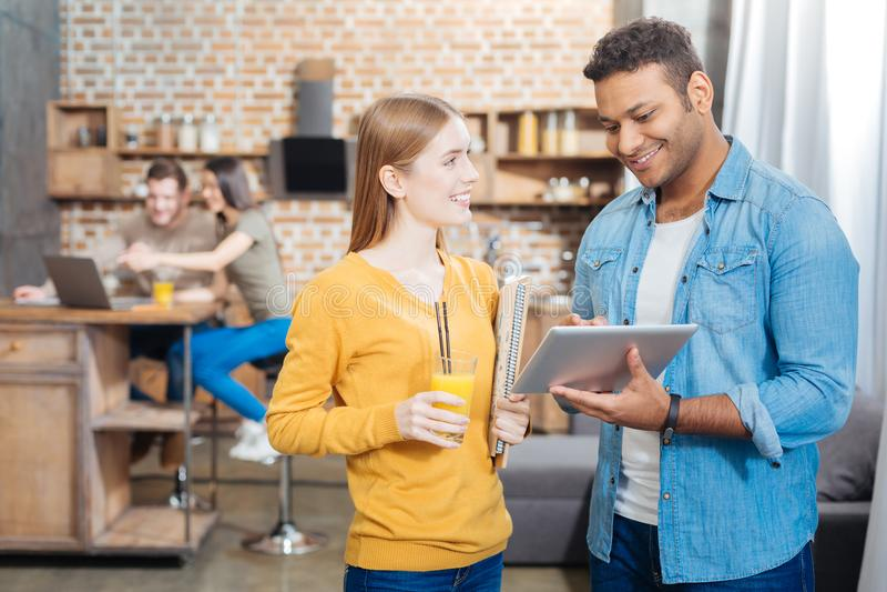 Estudiante alegre que detiene su jugo y a un hombre joven que se coloca con la tableta fotografía de archivo libre de regalías