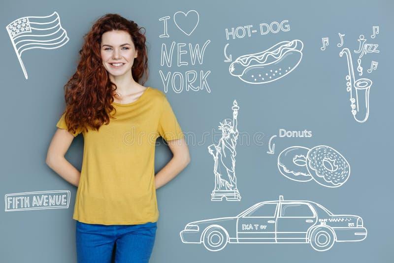 Estudiante alegre que sonríe mientras que sueña sobre viajar a Nueva York foto de archivo libre de regalías