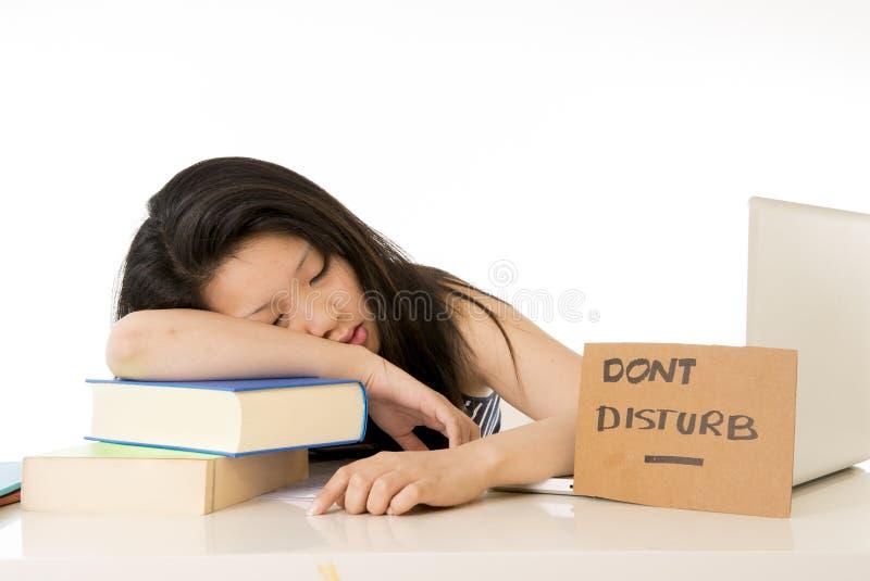 Estudiante asiático bastante chino dormido en el ordenador portátil imagenes de archivo