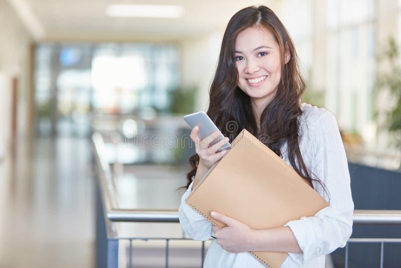 Estudiante asiático con la sonrisa del smartphone imagen de archivo