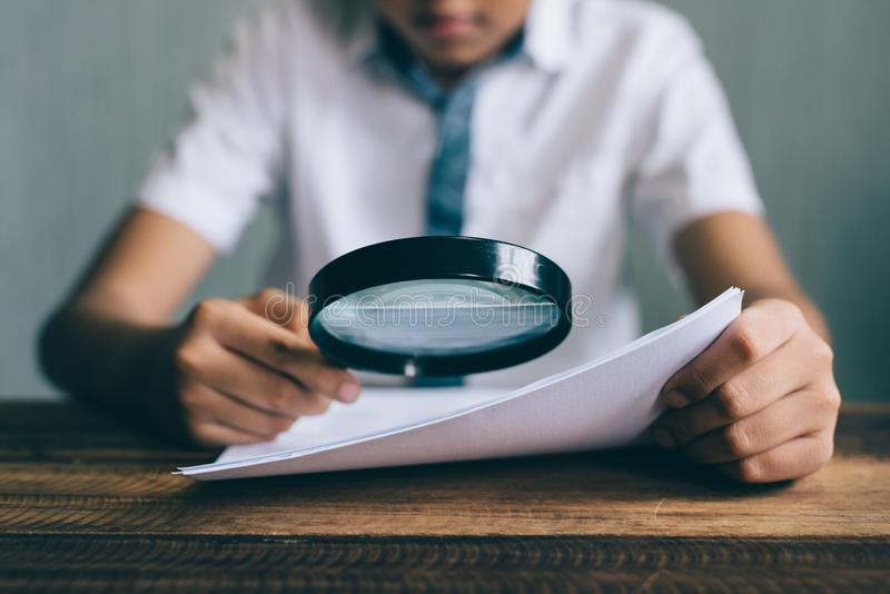 Estudiante asiático del muchacho que mira el papel usando la lupa fotos de archivo