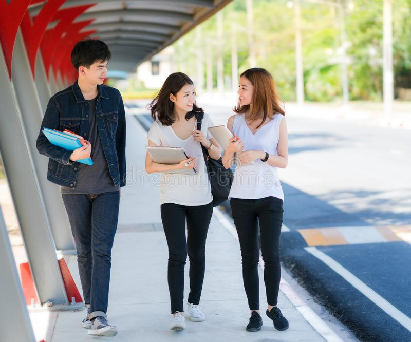 Estudiante asiático en juego de la universidad, paseo y togater de la charla en la calzada imagen de archivo libre de regalías