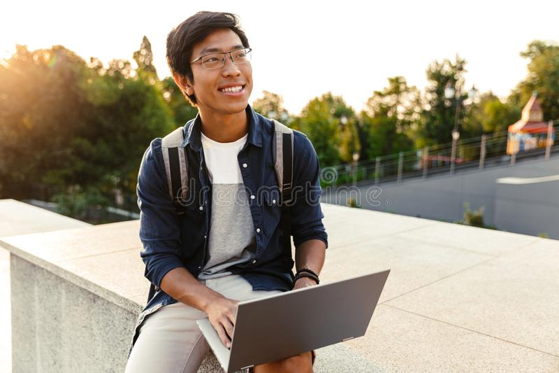 Estudiante asiático feliz del hombre con la mochila imágenes de archivo libres de regalías