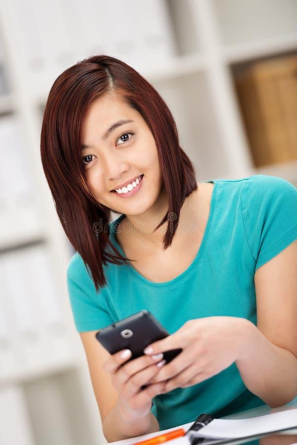 Estudiante asiático hermoso que manda un SMS en su móvil foto de archivo libre de regalías