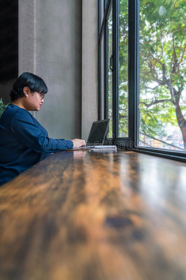 Estudiante asiático que usa el ordenador portátil en el café rústico de la opinión del jardín fotografía de archivo libre de regalías