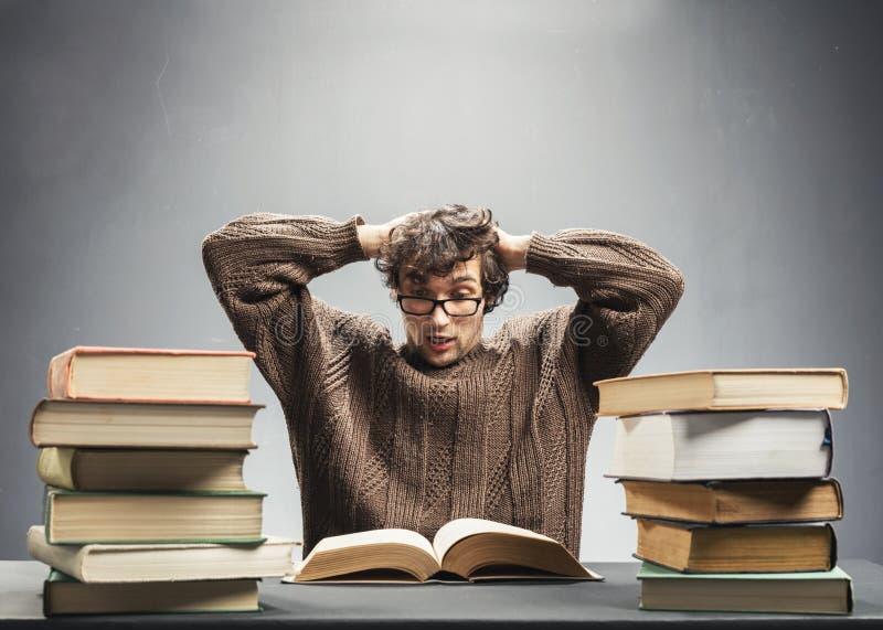 Estudiante aterrorizado que lee un libro foto de archivo
