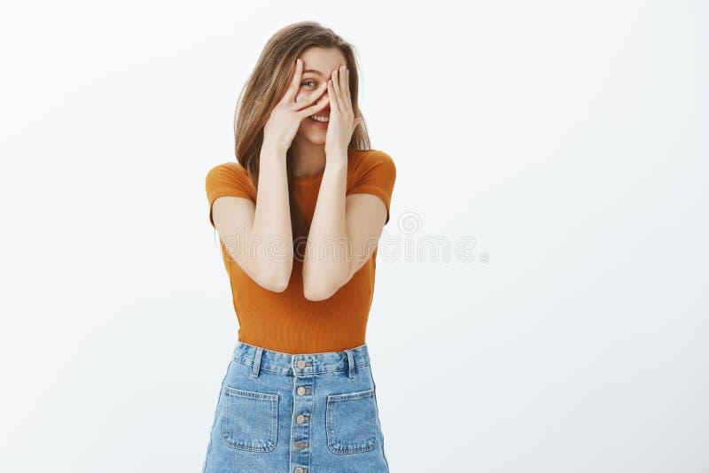 Estudiante atractivo coqueto en el equipo casual, cubriendo ojos y sonriendo ampliamente mientras que mira a escondidas a través  foto de archivo libre de regalías