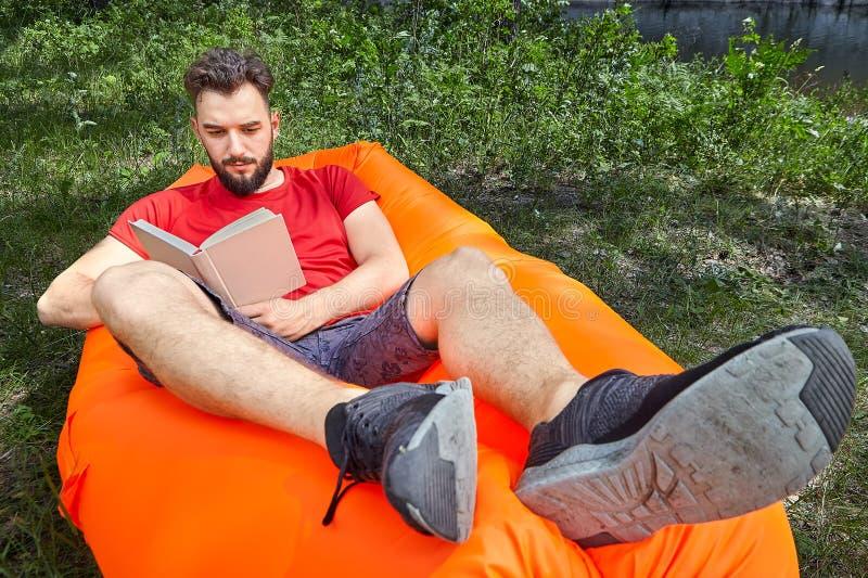 Estudiante barbudo con el libro en ocioso inflable imágenes de archivo libres de regalías