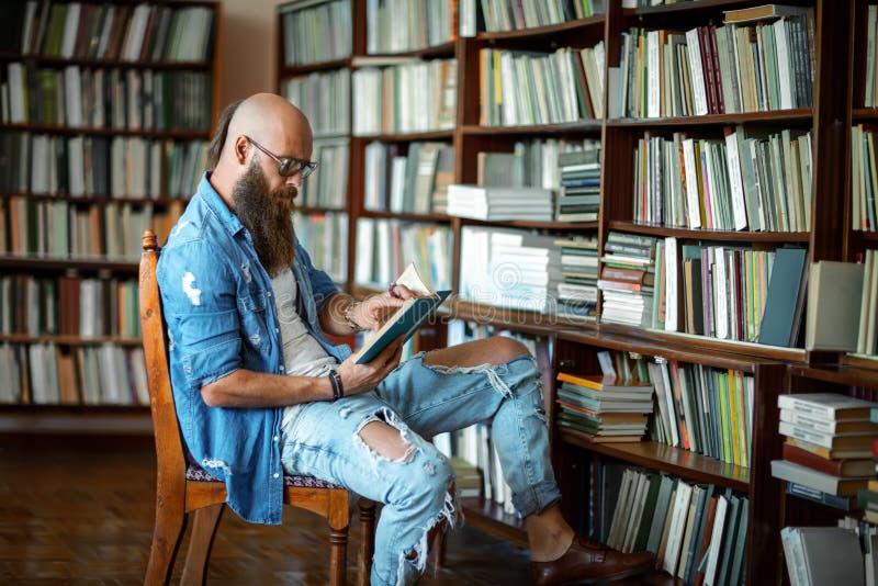Estudiante barbudo del inconformista que estudia en biblioteca fotografía de archivo libre de regalías