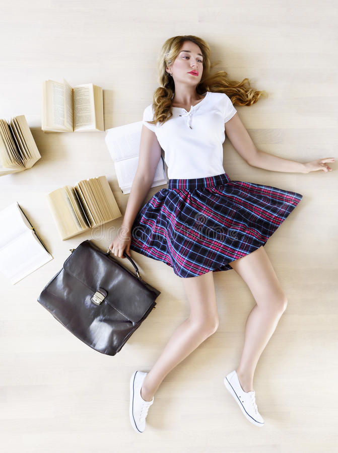 Estudiante bastante adolescente que sostiene el bolso y los libros de escuela con una expresión triste imágenes de archivo libres de regalías