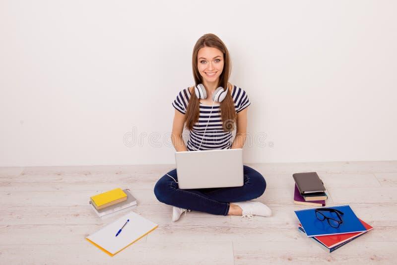 Estudiante bastante joven en camiseta rayada, vaqueros y headph fotografía de archivo libre de regalías