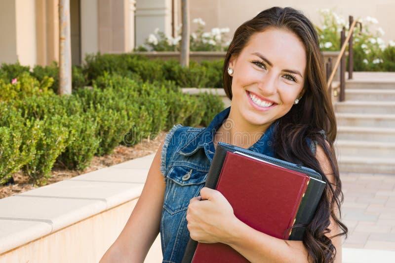 Estudiante bonita de la raza mixta con los libros de escuela en campus foto de archivo libre de regalías