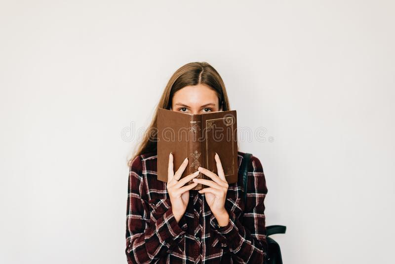 Estudiante bonita del adolescente con el libro en sus manos que ocultan la cara con el fondo del espacio y del blanco de la copia foto de archivo