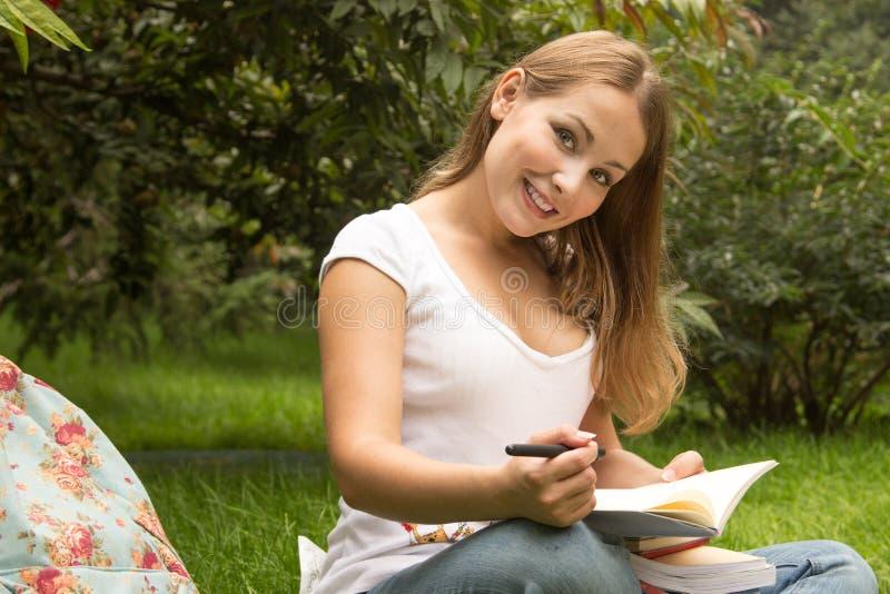 Estudiante bonito joven con los libros que trabajan en un parque foto de archivo libre de regalías