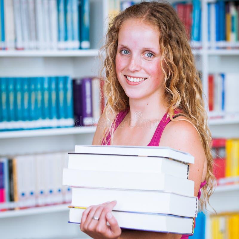 Estudiante bonito, joven del estudiante universitario en una biblioteca fotos de archivo