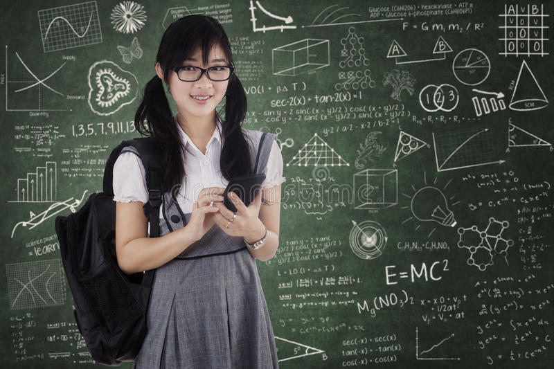 Estudiante bonito que usa el teléfono móvil para mandar un SMS imagen de archivo