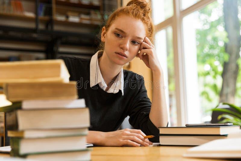Estudiante cansado confuso de la señora del pelirrojo que se sienta en la tabla con los libros en notas de la escritura de la bib fotografía de archivo libre de regalías