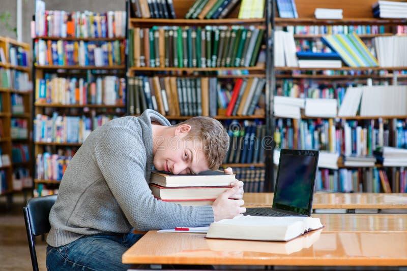 Estudiante cansado en la biblioteca de universidad imágenes de archivo libres de regalías