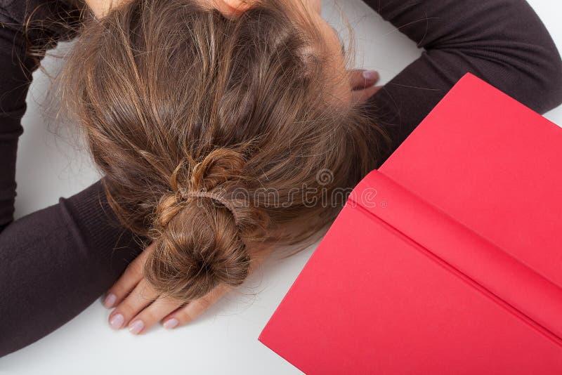 Estudiante cansado en un escritorio imagenes de archivo