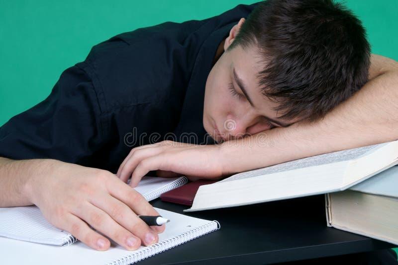 Estudiante cansado que duerme en el escritorio imagenes de archivo