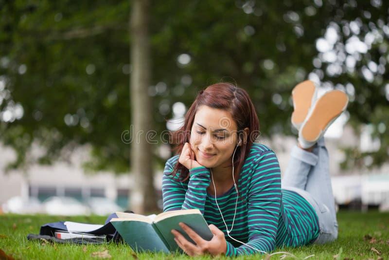 Estudiante casual sonriente que miente en la lectura de la hierba fotografía de archivo libre de regalías
