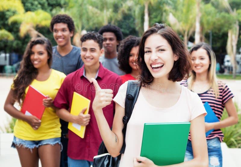 Estudiante caucásico que muestra el pulgar con el grupo de international imagen de archivo