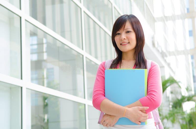 Estudiante chino asiático de la universidad con el fondo del campus imagen de archivo