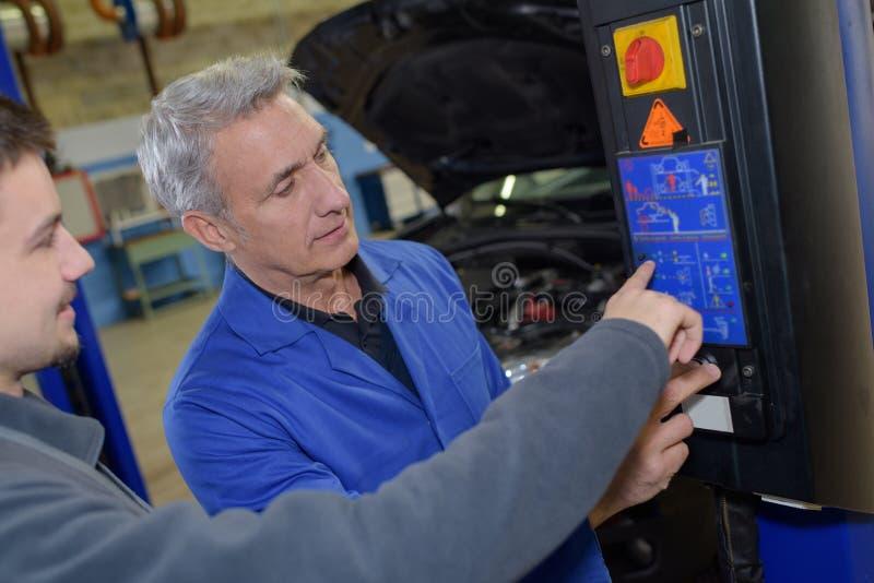 Estudiante con el instructor que repara el coche durante aprendizaje imagen de archivo libre de regalías