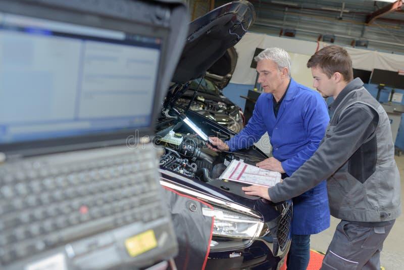 Estudiante con el instructor que repara el coche durante aprendizaje imagen de archivo