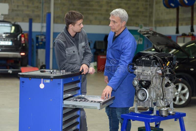 Estudiante con el instructor que repara el coche durante aprendizaje fotografía de archivo libre de regalías