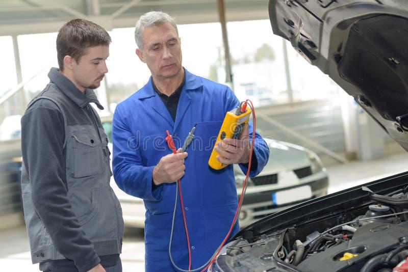 Estudiante con el instructor que repara el coche durante aprendizaje foto de archivo libre de regalías
