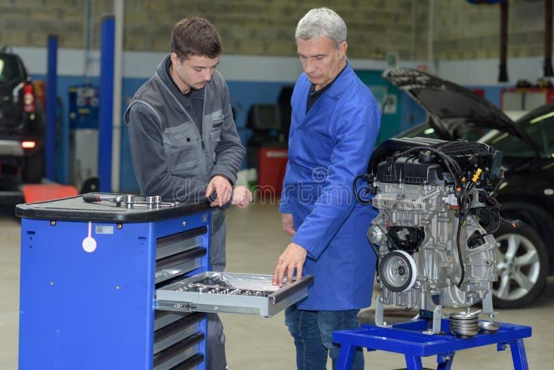 Estudiante con el instructor que repara el coche durante aprendizaje foto de archivo
