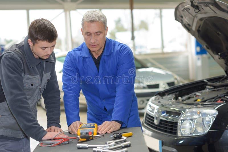 Estudiante con el instructor que repara el coche durante aprendizaje imágenes de archivo libres de regalías