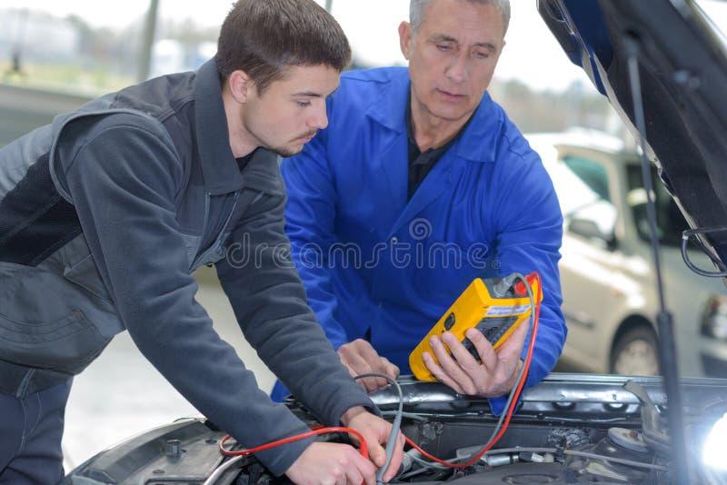 Estudiante con el instructor que repara el coche durante aprendizaje fotos de archivo