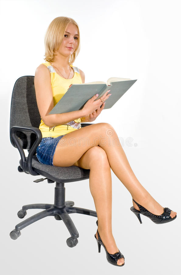 Estudiante con el libro en una silla fotos de archivo