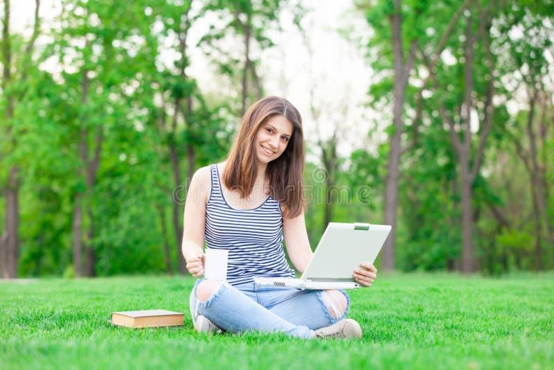 Estudiante con el ordenador portátil y la taza fotografía de archivo libre de regalías