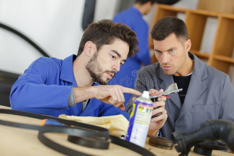 Estudiante con el profesor que estudia al mecánico automotriz fotografía de archivo libre de regalías