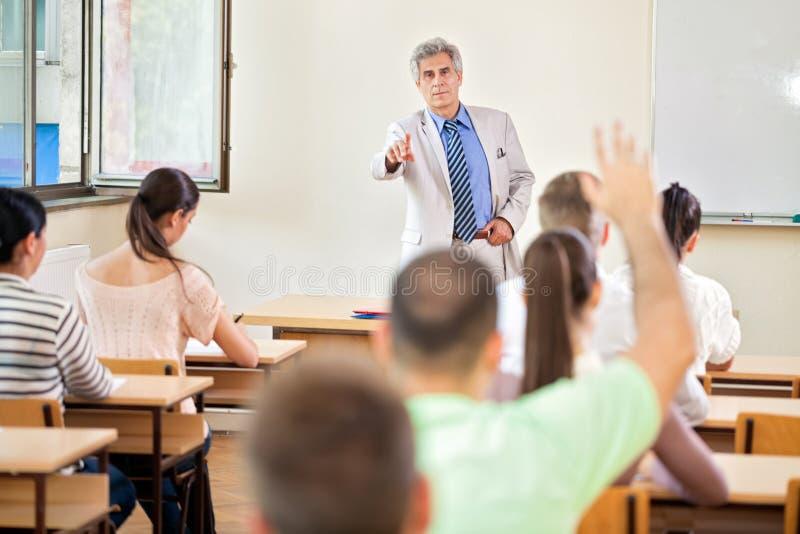 Estudiante con la mano para arriba en clase fotografía de archivo libre de regalías