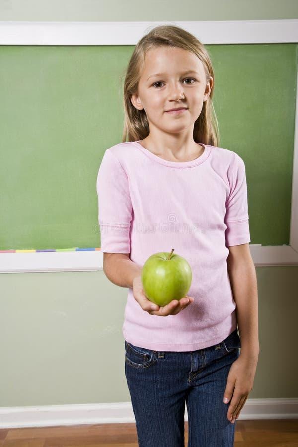 Estudiante con la manzana para el profesor fotos de archivo