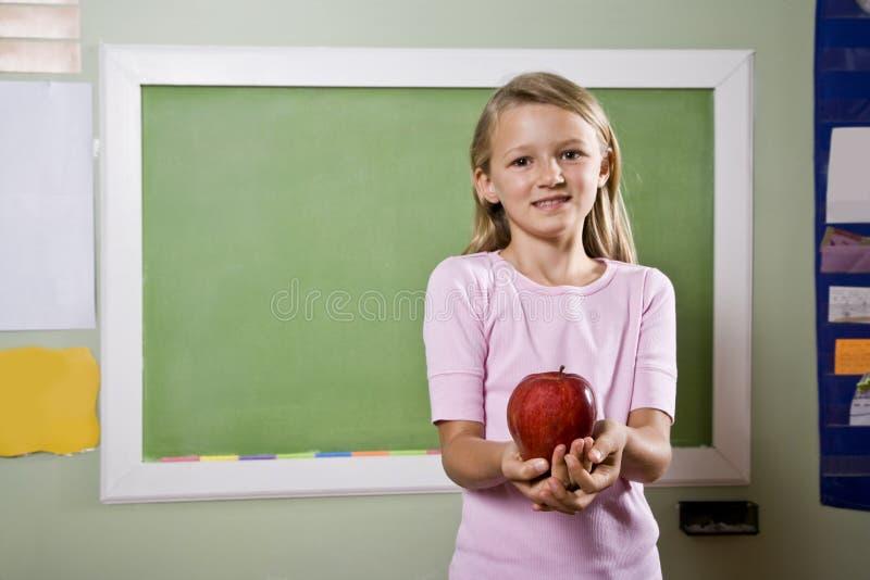 Estudiante con la manzana para el profesor foto de archivo