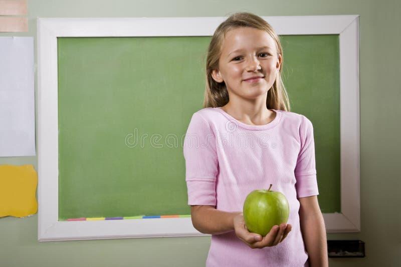 Estudiante con la manzana para el profesor imagen de archivo