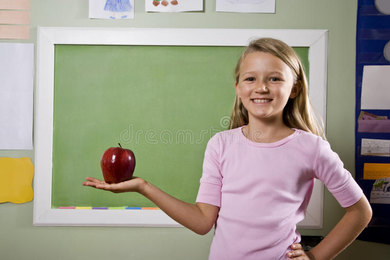 Estudiante con la manzana para el profesor imagenes de archivo